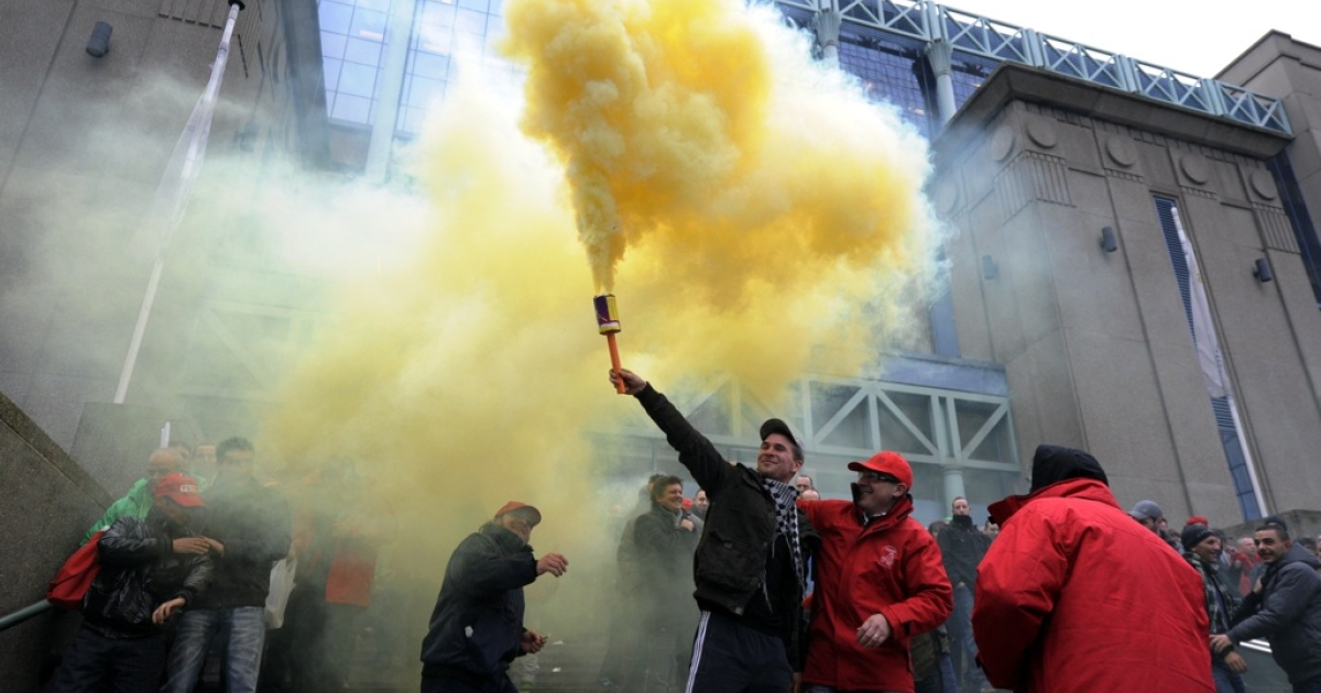 A man holds a smoke flare during a demonstration called by Belgian unions against the new government's austerity measures, in Brussels on December 2, 2011. Euro zone leaders are discussing the possibility of resuscitating a new Bolkestein directive to remove trade barriers in Europe's services sector. Dutch politician Frits Bolkestein devised the plan in 2006 but met heavy opposition.</p>