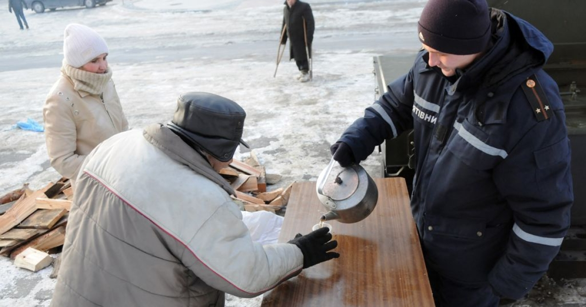 An elderly man receives hot food and drink at an emergency shelter in the western Ukrainian city of Lviv, on January 30, 2012.</p>