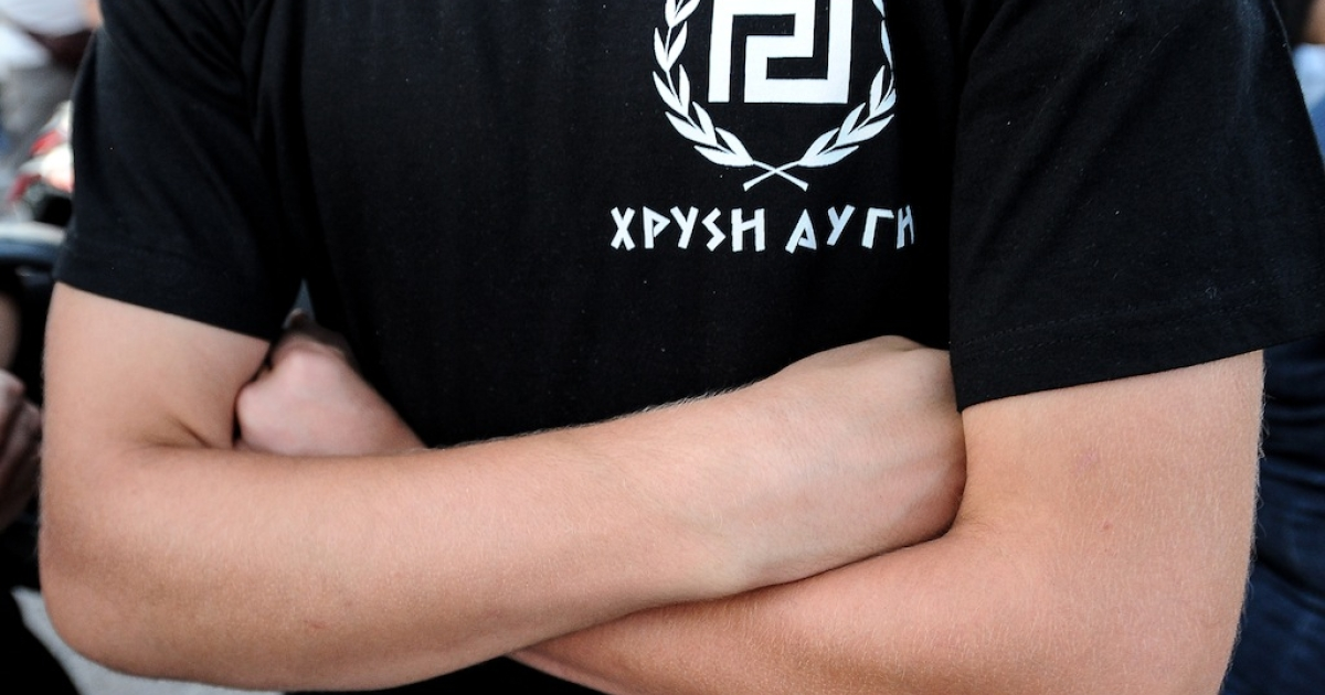 A supporter of extreme-right ultra nationalist party Golden Dawn (Chryssi Avghi), waits during a rally in Athens in June. Many accuse the party of being complicit in vigilante violence and using neo-Nazi, anti-immigrant rhetoric.</p>