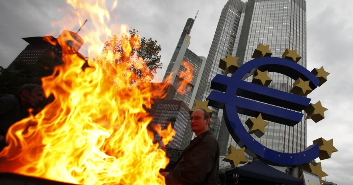 A pedestrian walks in front of the headquarters of the European Central Bank on Oct. 18, 2011 in Frankfurt, Germany. Around hundred protesters operate a camp outside the ECB to demonstrate against economic and financial policy.</p>