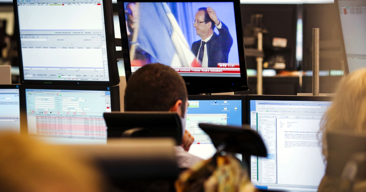 Brokers sit in front of their computer screens and a TV screen displaying an image of incoming French President Francois Hollande, on May 7, 2012 at the German stock exchange in Frankfurt. Shares on the top German stock market fell sharply at the open as investors digested the results of elections in France and Greece that appeared to show voters rejecting eurozone austerity.</p>