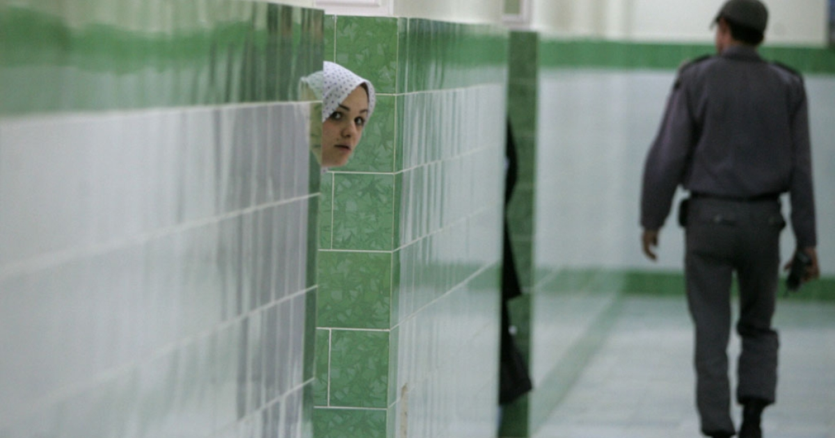An Iranian inmate peers from behind a wall as a guard patrols the female section of Evin prison in Tehran, Iran, in this 2006 file photo.</p>