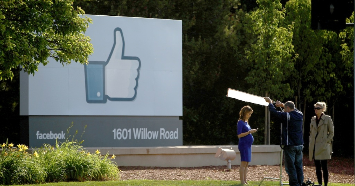 A television crew prepares for a broadcast in front of a 'like' sign outside Facebook headquarters May 18, 2012 in Menlo Park, California. The eight-year-old social network company listed their initial public offering on NASDAQ at $38 a share, a valuation of $104 billion, making its IPO the third largest in U.S. history after General Motors and Visa.</p>