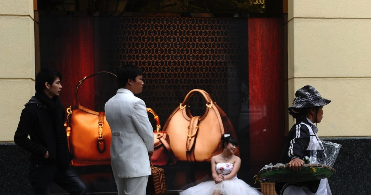 A young couple poses for their wedding photos outside a Gucci store in Hanoi on December 6, 2012.</p>