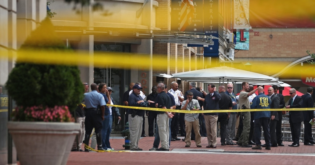 Local and federal investigators gather evidence after a security guard was shot in the arm at the headquarters of the Family Research Council on Aug. 15, 2012, in Washington, DC.</p>
