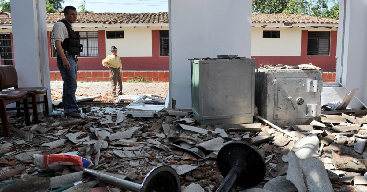 A policeman and a local resident look at the ruins of a Bank office after a bombing attack by the Revolutionary Armed Forces of Colombia (FARC) guerrillas.The FARC are suspected of bombing two police stations in Colombia in the past week.</p>