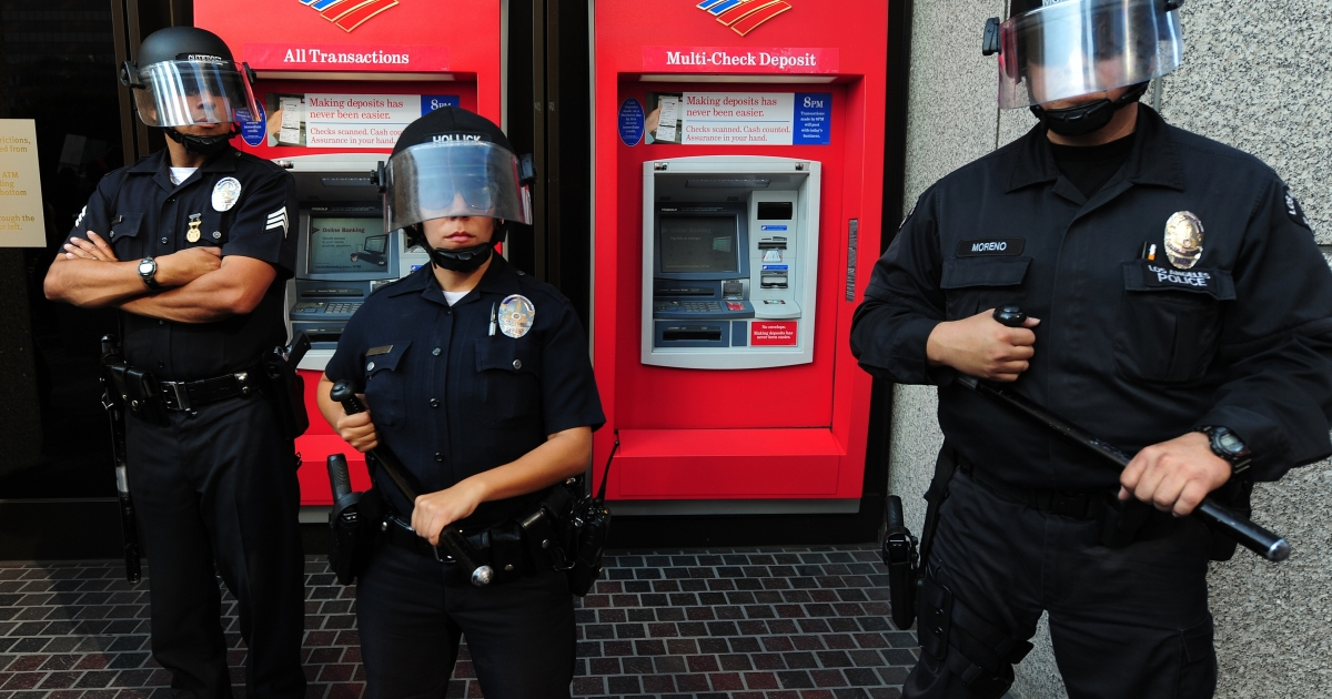 Police guard the ATM machines in front of a Bank of America branch in Los Angeles following an anti-Wall Street protest on Nov. 17, 2011.</p>