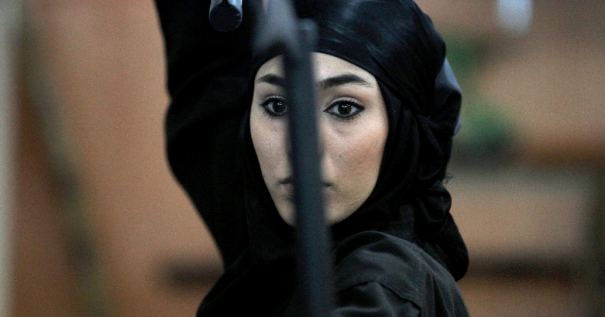 An Iranian female Ninja demonstrates her Ninjutsu skills in a martial arts club during a showcase for the media in the city of Karaj, 40 kms west of the capital Tehran, on March 15, 2012.</p>