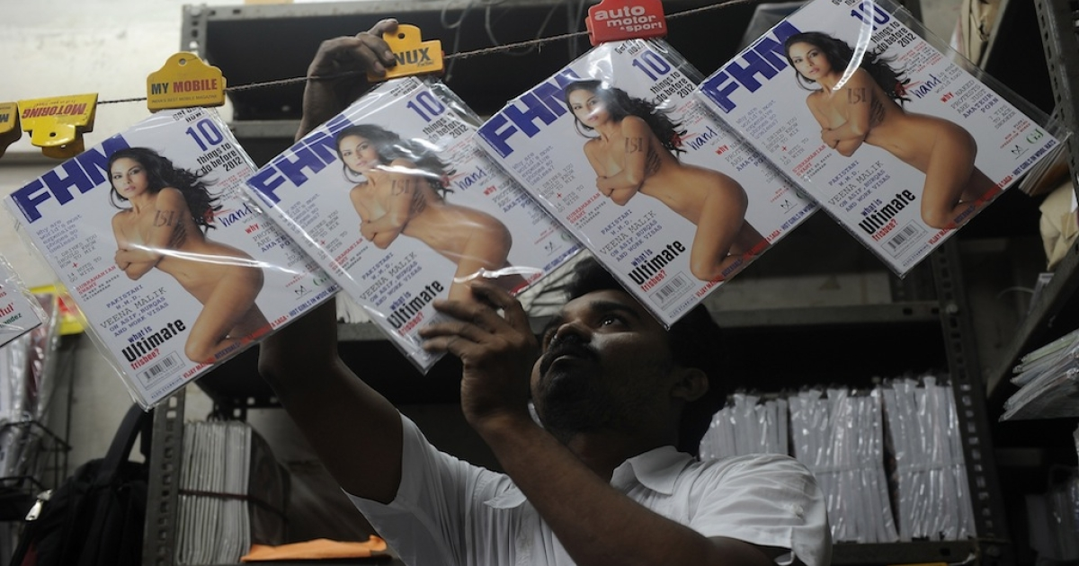 A bookstore employee displays copies of the FHM magazine upon delivery in Mumbai on December 5, 2011. India's version of FHM magazine has defended the cover of its December issue, which shows a nude Pakistani actress with the initials of Pakistan's powerful intelligence agency displayed on her arm. A preview of the cover on the magazine's website triggered a media frenzy which intensified when actress Veena Malik denied posing nude and accused FHM of doctoring her image.</p>