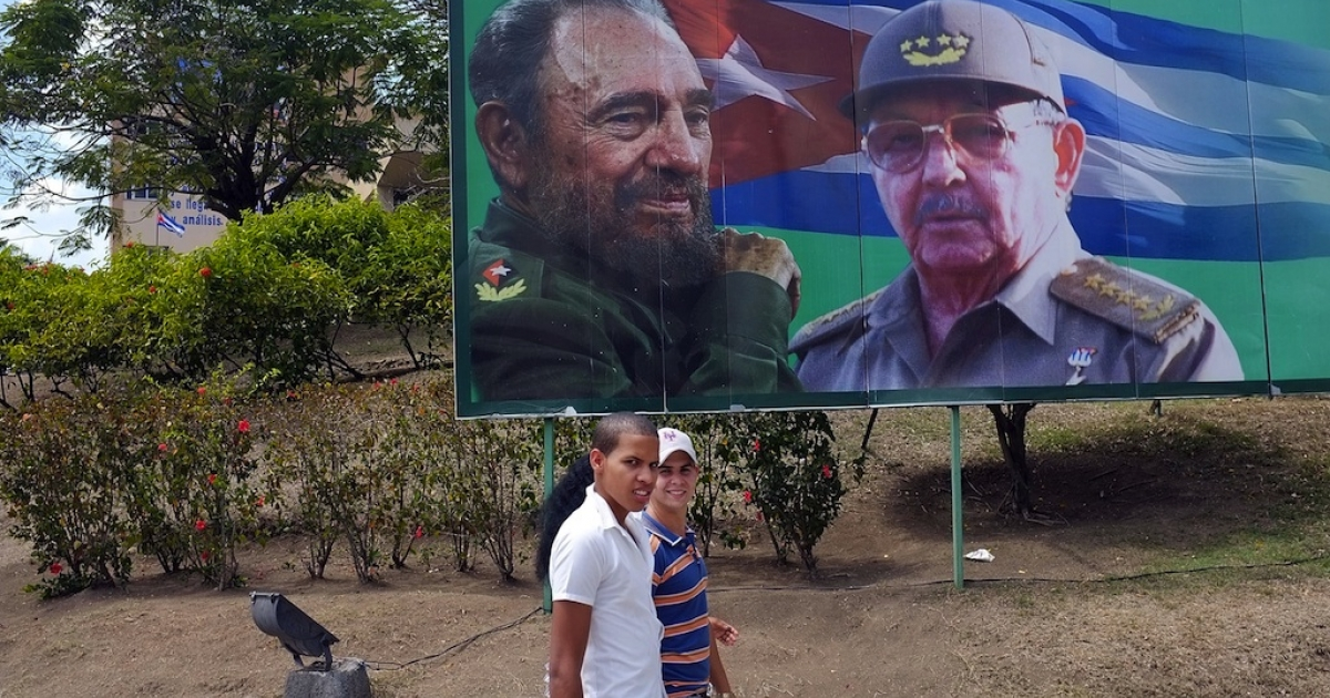 Two teenagers walk past a billboard of Fidel and Raul Castro.</p>