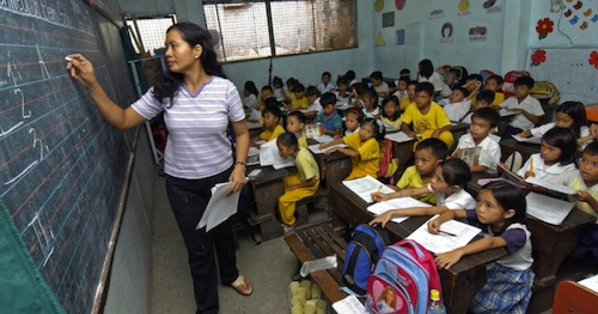 Manila, PHILIPPINES: Teacher Leonora Jusay gives a lesson to her 59 students of a Grade 2 class, packed in small classroom that was a former toilet of the government-run Commonwealth Elementary School in suburban Manila in 2006. The dire situation in this overcrowded public school has become symbolic of the Philippines' educational system as a whole -- too few resources used to educate too many students in too little time.</p>