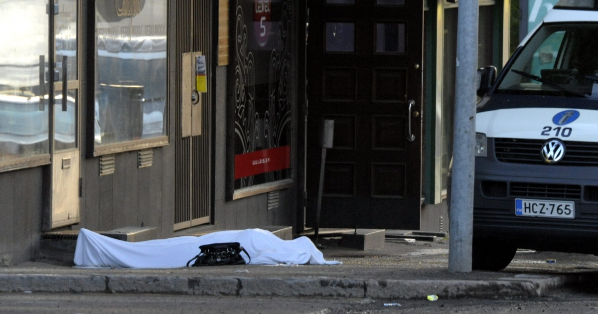 The body of a shooting victim lies covered with a sheet as Police cordon off the area following multiple shootings by a gunman in Hyvinkaa, Finland, May 26, 2012.</p>