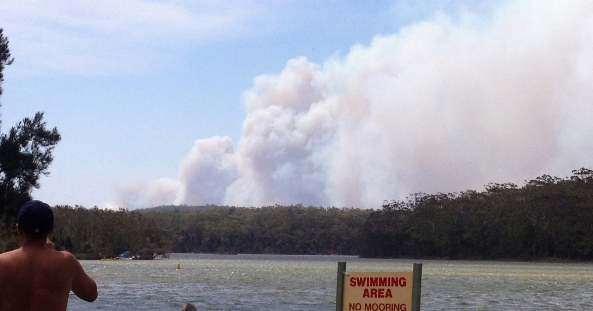 This picture taken from Lake Conjola shows bathers looking on as smoke billows from a bushfire (back) at Deans Gap in New South Wales on January 8, 2013.</p>
