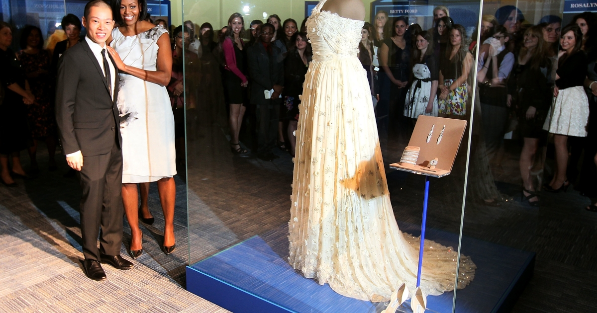 First lady Michelle Obama stands with designer Jason Wu in front of her 2009 inaugural gown on Mar. 9, 2010, at the Smithsonian Museum of American History.</p>