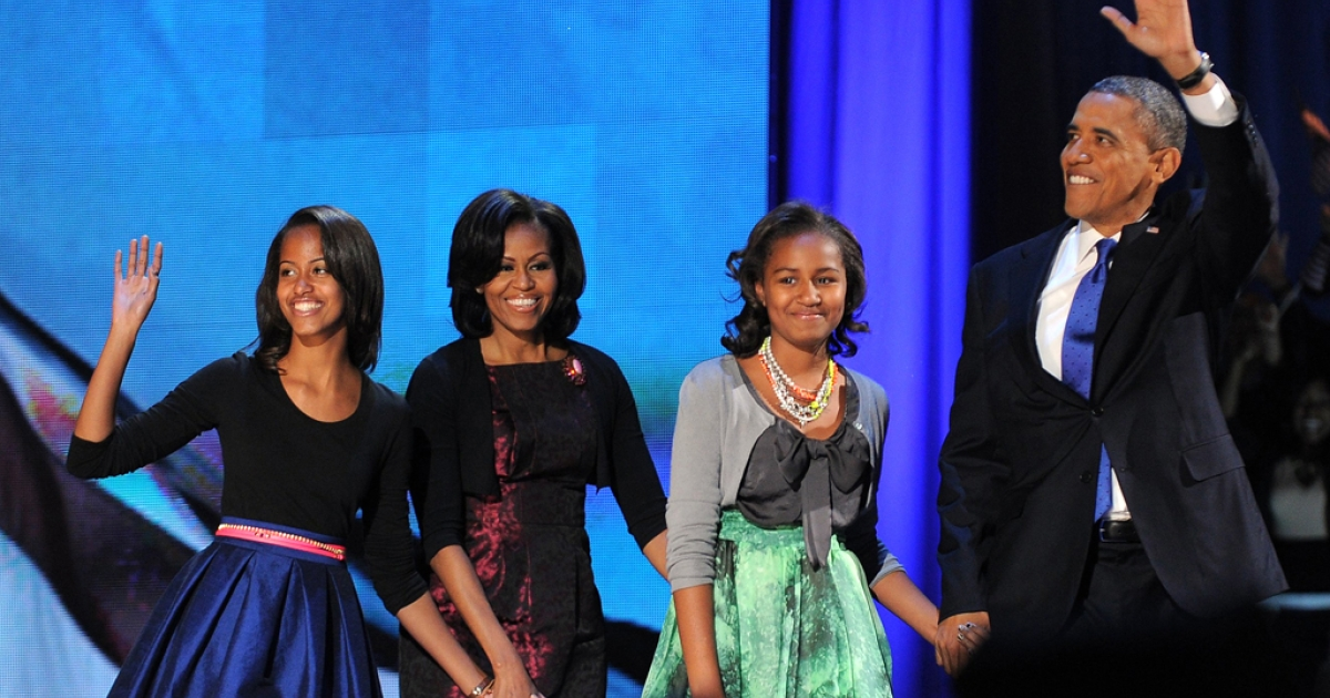 US President Barack Obama accompanied by daughter Malia, First Lady Michelle and daughter Sasha waves to supporters as he arrives on stage on election night November 6, 2012 in Chicago, Illinois.</p>