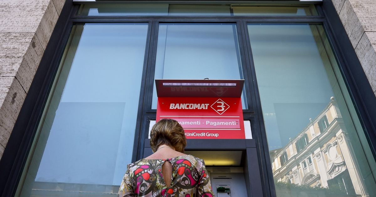 A customer at an automatic teller machine at a Unicredit Bank branch in Rome on September 2011. The Fitch ratings agency has joined Moody's and Standard &amp; Poor's in downgrading Italy's credit rating.</p>