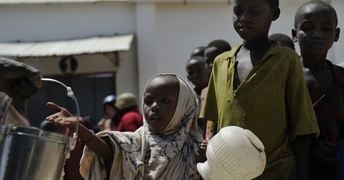 Displaced Somali children wait in line for food aid rations on January 19, 2012 at a UN distribution center in the capital Mogadishu. A new report by Transparency International warns that direct deliveries of food are prone to corruption.</p>