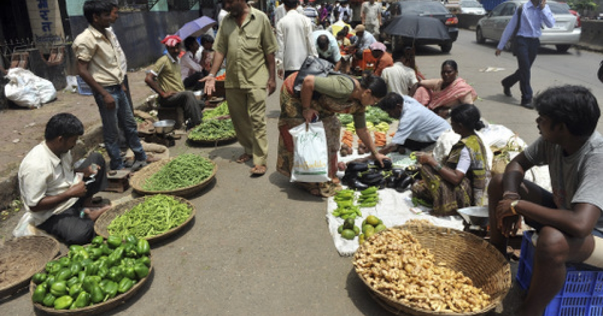 Indian customers haggle for prices before buying vegetables outside a wholesale market in Mumbai on September 14, 2011. Food inflation dropped significantly this week, ending more than a year of price increases and raising the possibility that the central bank may ease interest rates.</p>