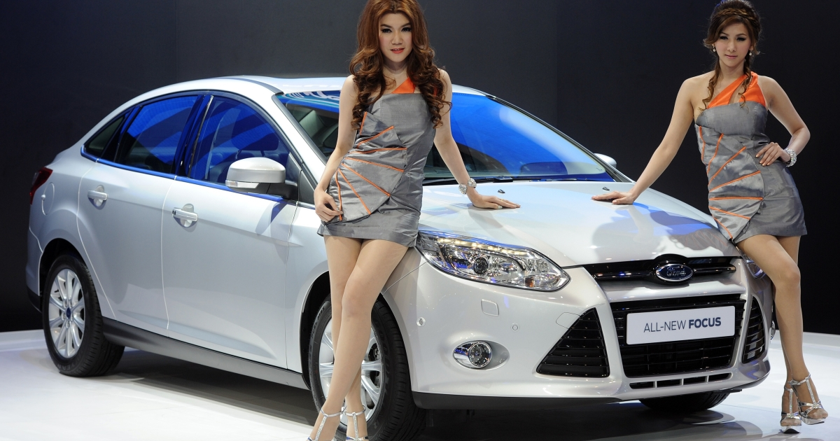 Thai models pose next to a Ford Focus on display at the 33rd Bangkok International Motor Show in Thailand on March 27, 2012.</p>