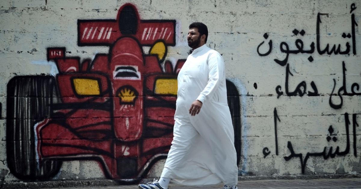 A man in Bahrain walks past graffiti calling for the cancellation of the Formula One Grand Prix in Bahrain later this month. The sign reads,
