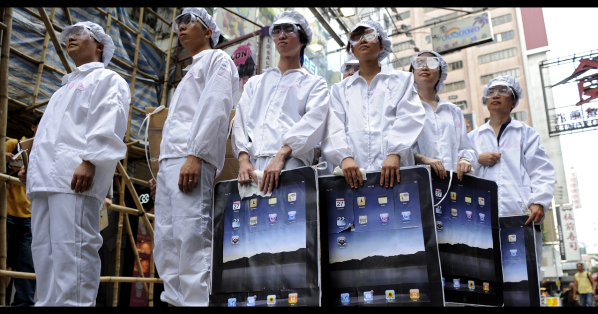 Participants dressed up to represent Foxconn workers take part in a protest against the Taiwanese technology giant, which manufactures Apple products in mainland China, outside an Apple retail outlet in Hong Kong on May 7, 2011. At least 13 Foxconn employees died in apparent suicides last year, which rights activists blamed on tough working conditions in a case that highlighted the challenges faced by millions of Chinese factory workers.</p>