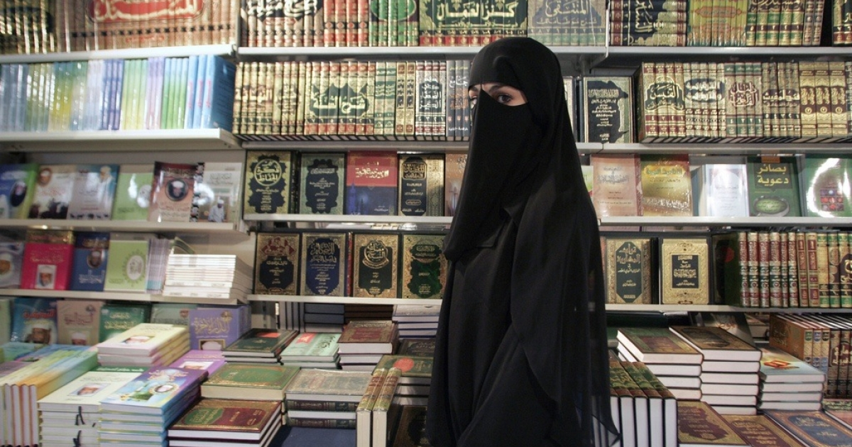 A young woman wearing the burka, the head-to-toe Islamic veil, passing a book shop in Le Bourget, close to Paris, on March 25, 2005.</p>