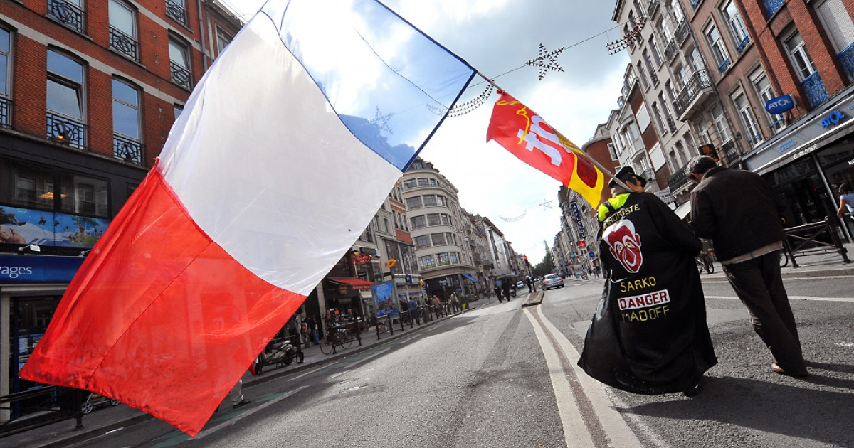 A demonstrator holds a French flag on September 7, 2010 in Lille, northern France, during a one-day national strike action against a government pension reform bill.</p>