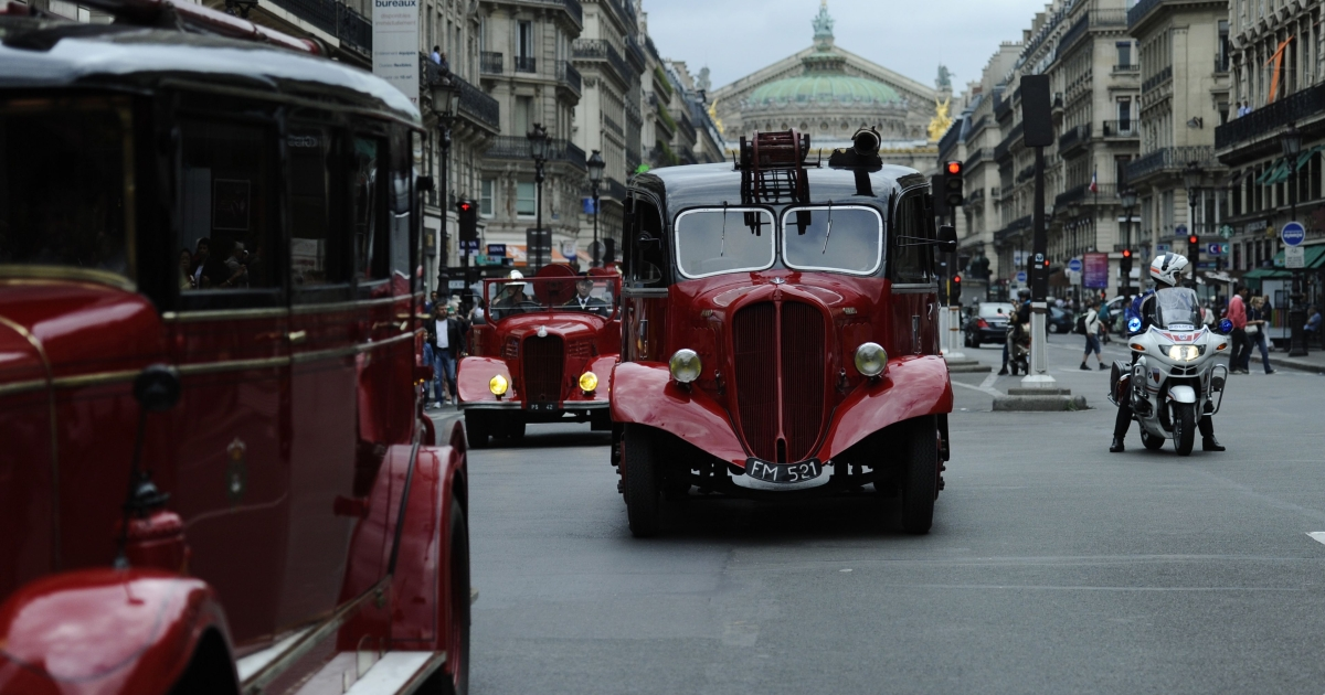 Firemen from the Paris brigade (Sapeurs-Pompiers de Paris) drive an old fire engine with the city's Opera Garnier in the background.</p>
