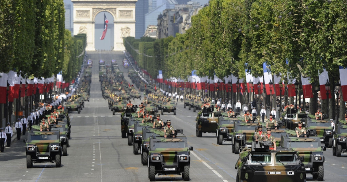 French army armored vanguard vehicles (VAB) lead jeeps as they drive down the Champs-Elysees with the Arc de Triomphe in the background, during the annual Bastille Day parade in Paris, on July 14, 2011.</p>