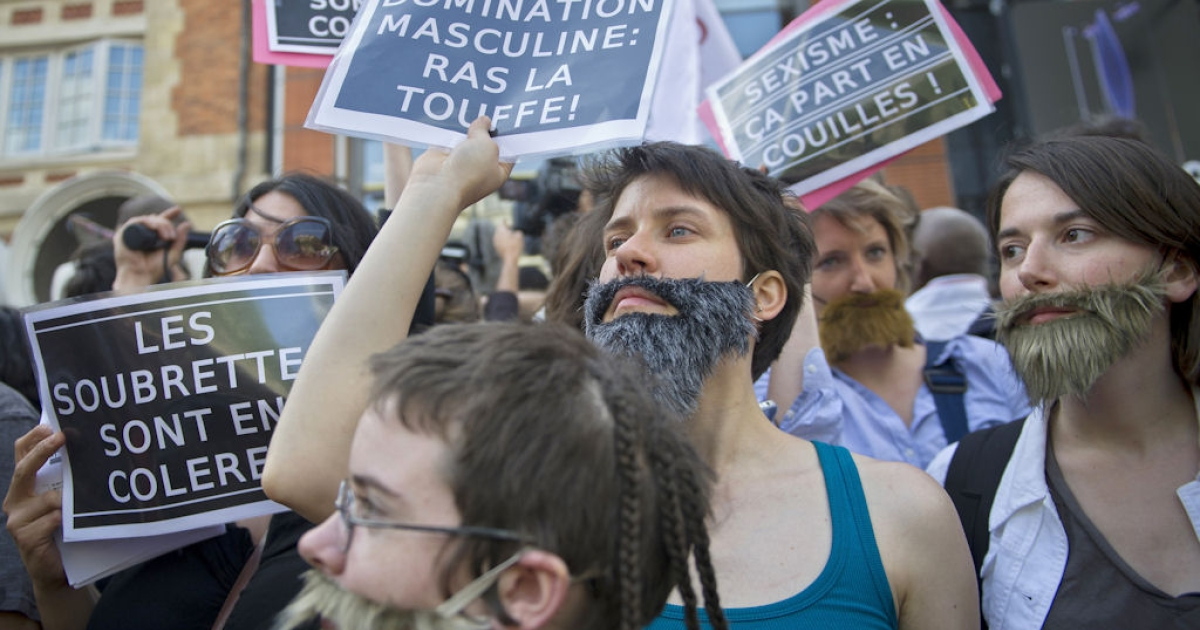 Women, mostly members of feminist groups, wear fake moustaches and beards and hold anti-sexist placards as they demonstrate in Paris on May 22, 2011 against the political and media reaction to the sexual assault allegations against former IMF chief Dominique Strauss-Kahn.</p>
