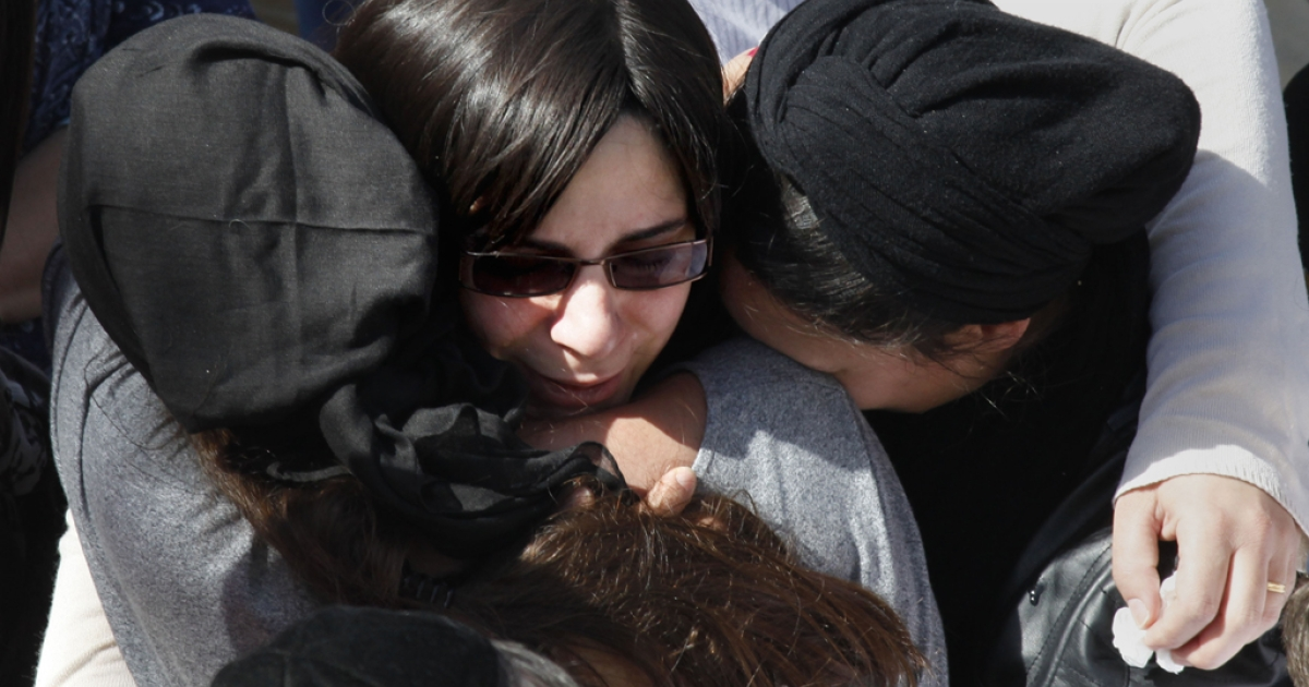 Friends and relatives comfort Eva Sandler, the wife of Jonathan Sandler, and the mother of Gabriel 4, Arieh 5, during their funeral at the Givat Shaul cemetery in Jerusalem on March 21, 2012. A new survey conducted by the Anti-Defamation League found that