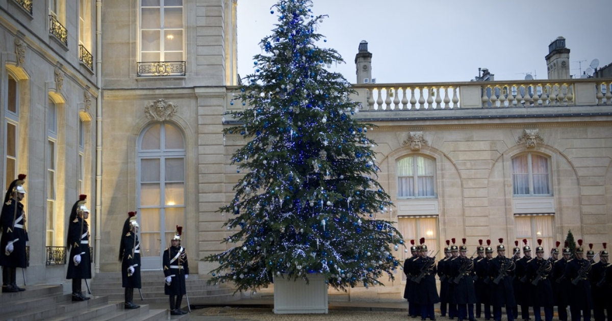Guards stand near a Christmas tree at the Elysee presidential palace in Paris. Some communities are adopting trees, and replanting them after the holidays.</p>