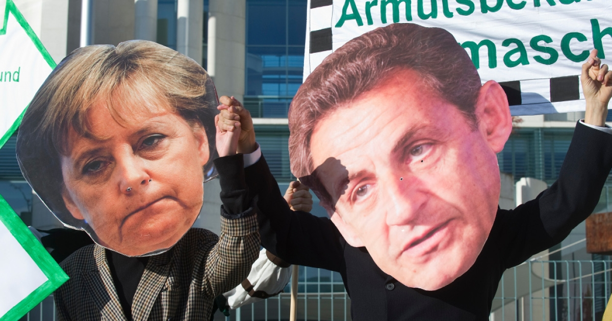 Protesters dressed as German Chancellor Angela Merkel and French President Nicolas Sarkozy demonstrate in Berlin on Oct. 21, calling on more spending to alleviate poverty, rather than to bailout banks. At the same time, the German Bundestag debated the European Stability pact, ahead of summit of EU leaders in Brussels that aims to thrash out a solution to the eurozone debt crisis.</p>
