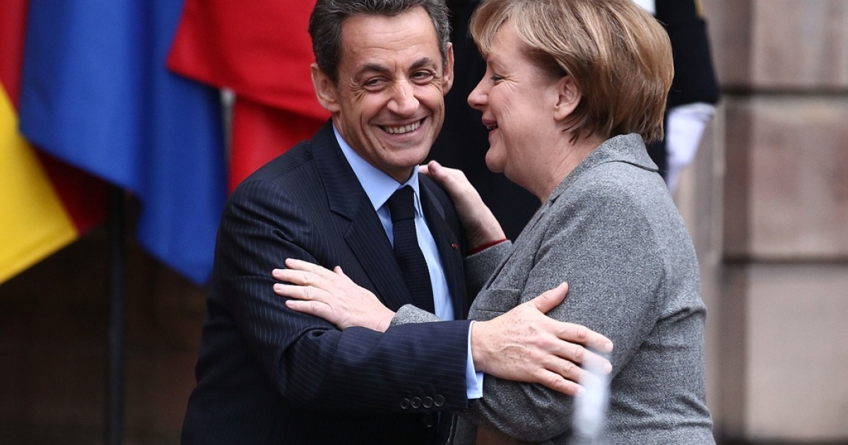 French President Nicolas Sarkozy and German Chancellor Angela Merkel prior to a meeting with Italian Prime Minister Mario Monti on November 24, 2011 in Strasbourg, France. French pundits say Sarkozy caved to a Merkel plan that won't work.</p>