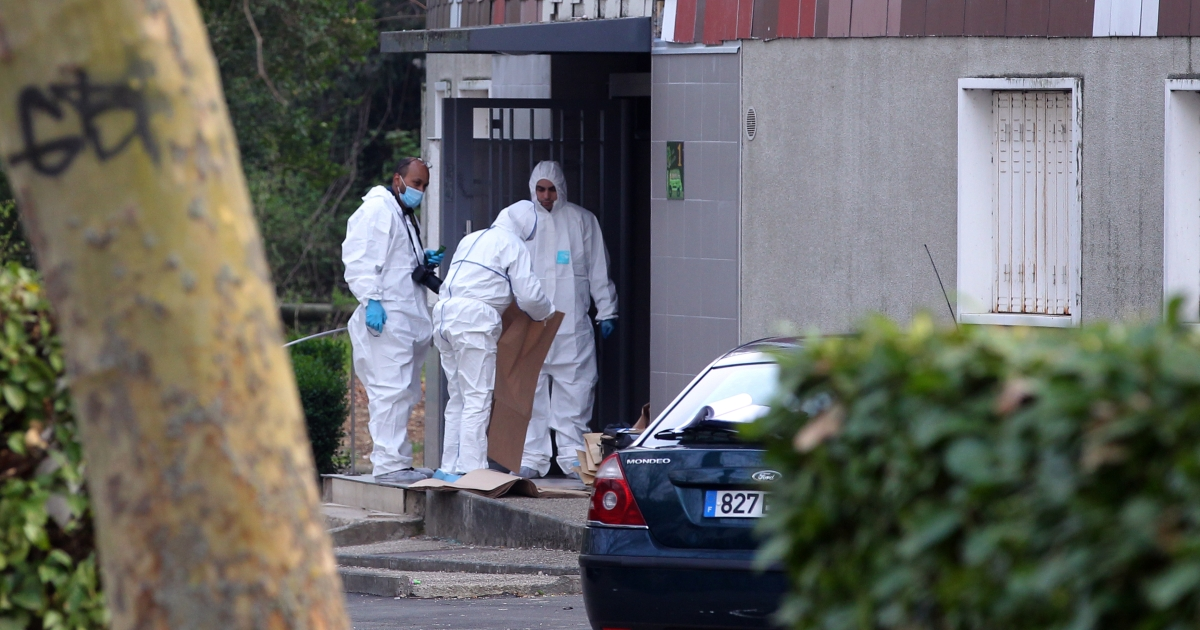 French forensic police are seen yesterday outside the home of a woman identified as Malika, 47, who was shot three times in the head and pronounced dead that evening.</p>