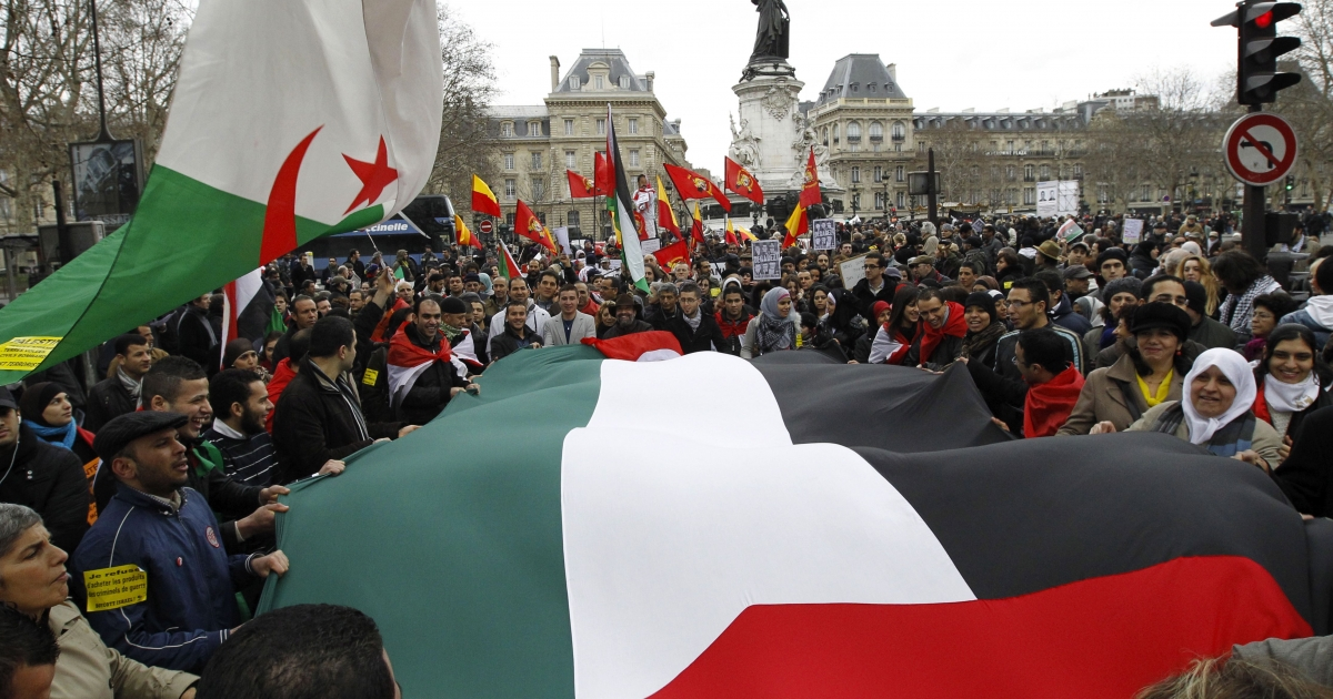 People hold a giant Palestinian flag during a demonstration to protest against war, racism and xenophobia on February 26, 2011 at Republic square in Paris.</p>
