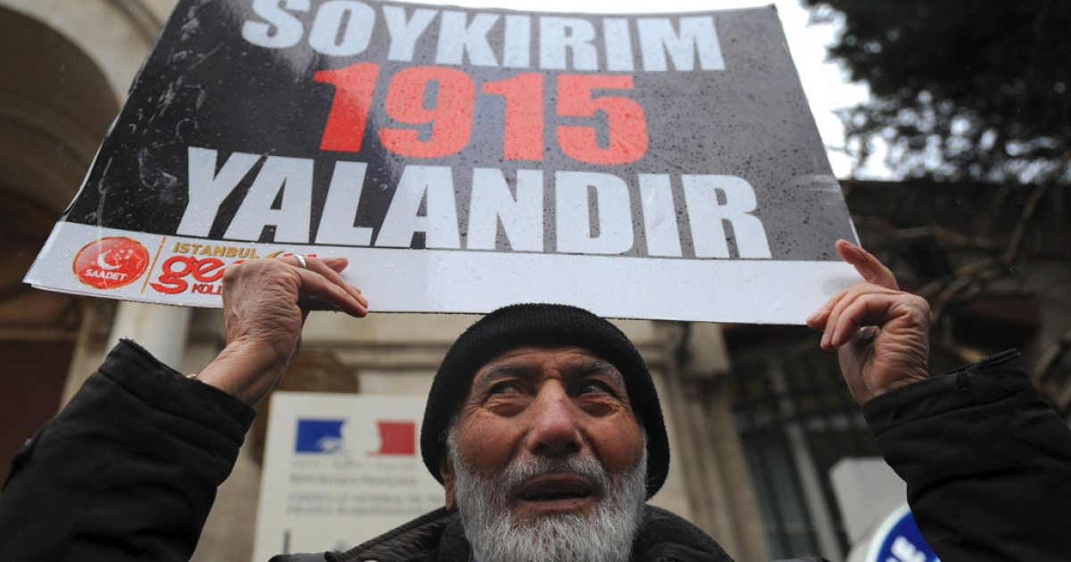 What's in a word?  When it comes to Genocide a lot.<br />A Turkish man holds a placard reading 'Genocide is a lie' in front of the French Consulate in Istanbul following vote in French Parliament making it a crime to deny the death of 1.5 million Armenians in 1915 at the hands of the Ottoman empire was genocide</p>