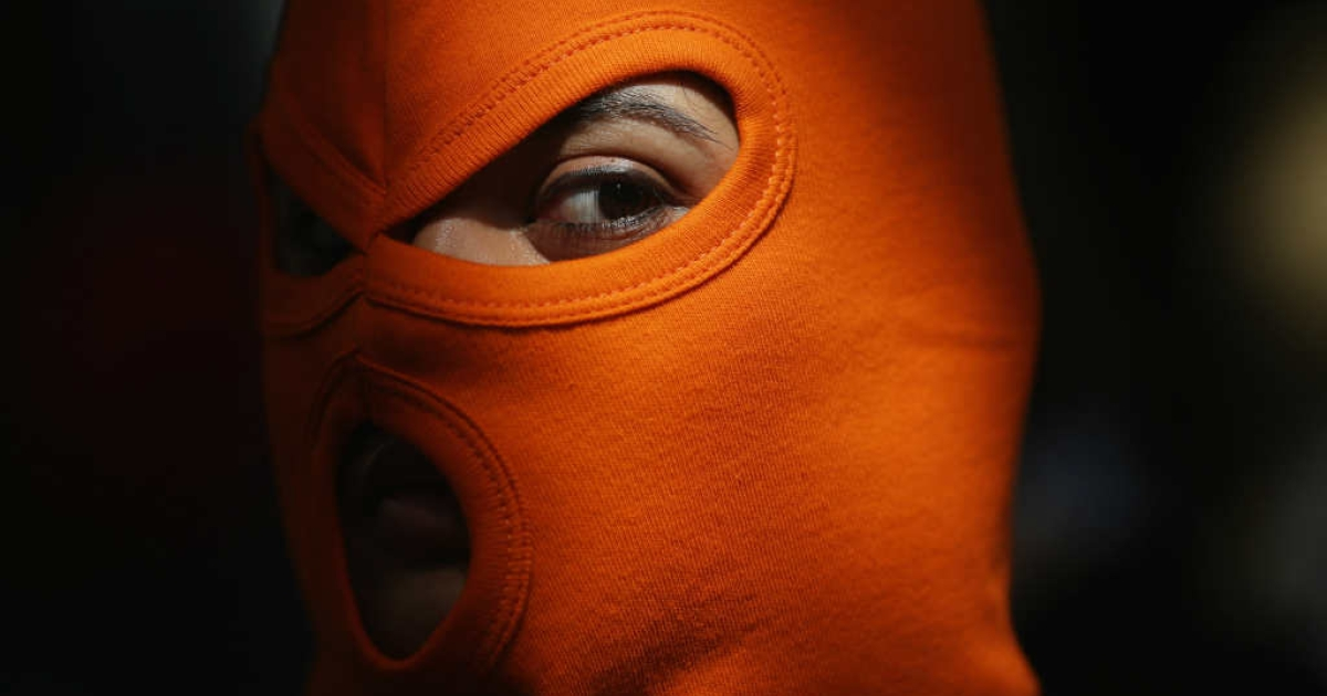 A person wears an orange mask as a demonstration by supporters of the jailed feminist punk band 'Pussy Riot' taking place outside the Russian Embassy. Pussy Riot has also found support from various celebrities.</p>