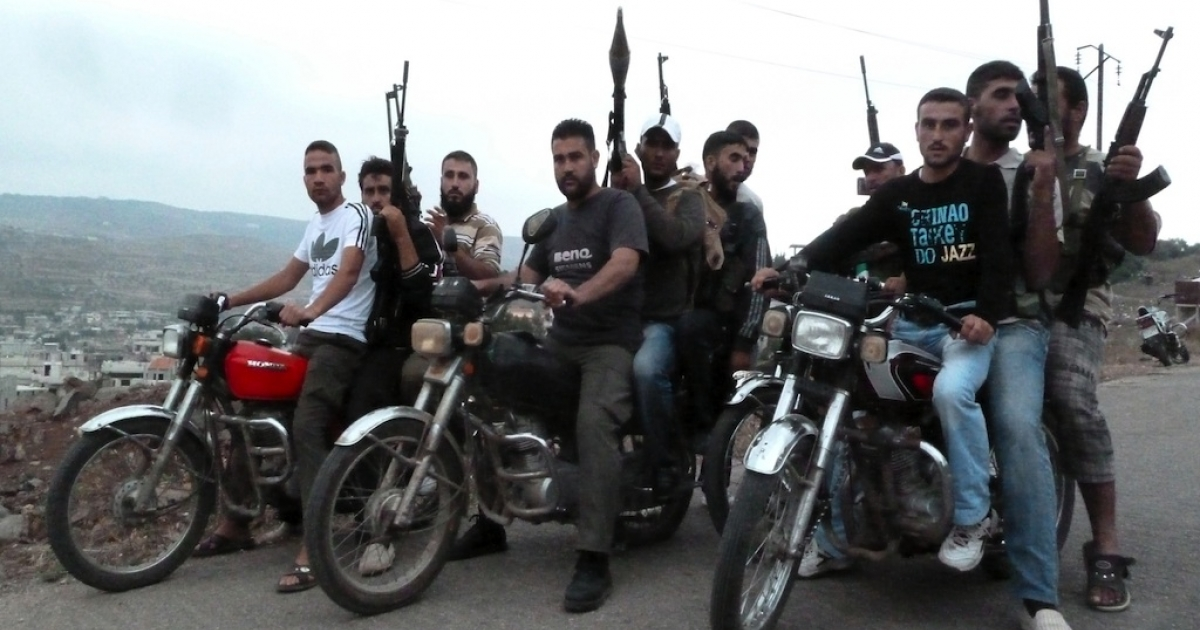 Members of the Free Syrian Army ride motorbikes in the village of Azzara on the outskirts of flashpoint city of Homs on June 28, 2012.</p>