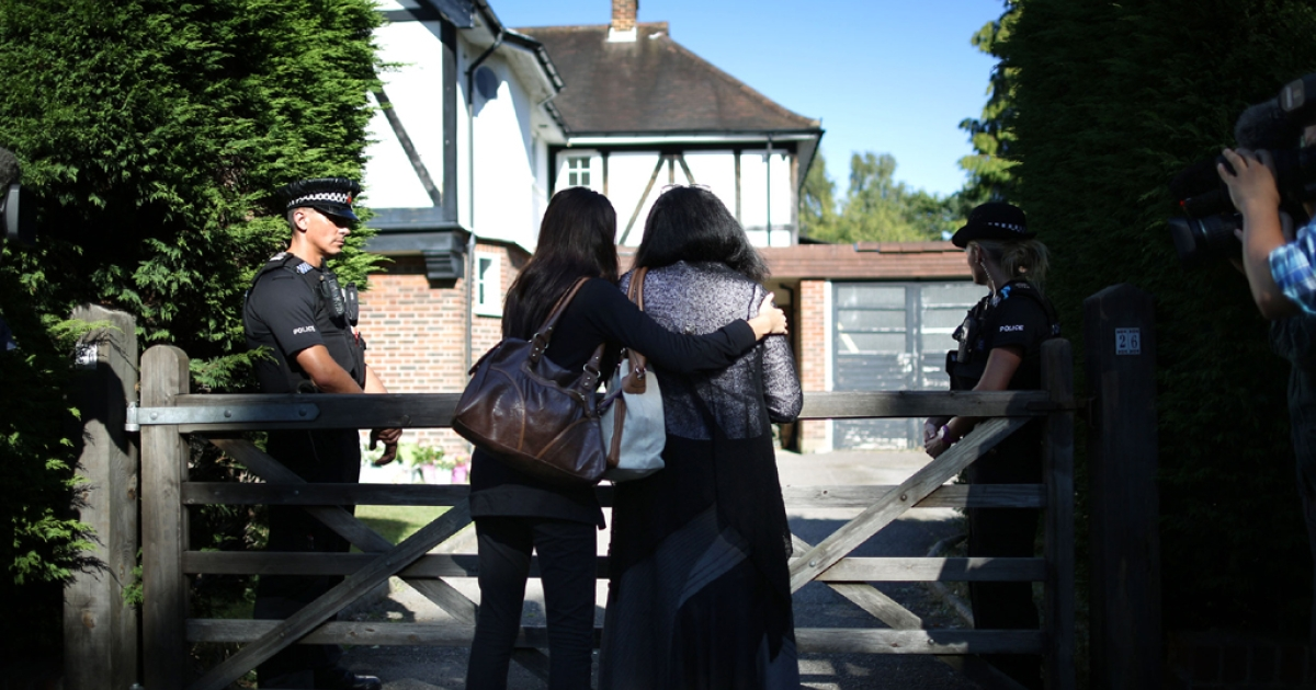 Two women, who identified themselves as family friends, hold each other as they stand at the front gate of the house of the al-Hilli family on September 7, 2012 in Claygate, England.</p>