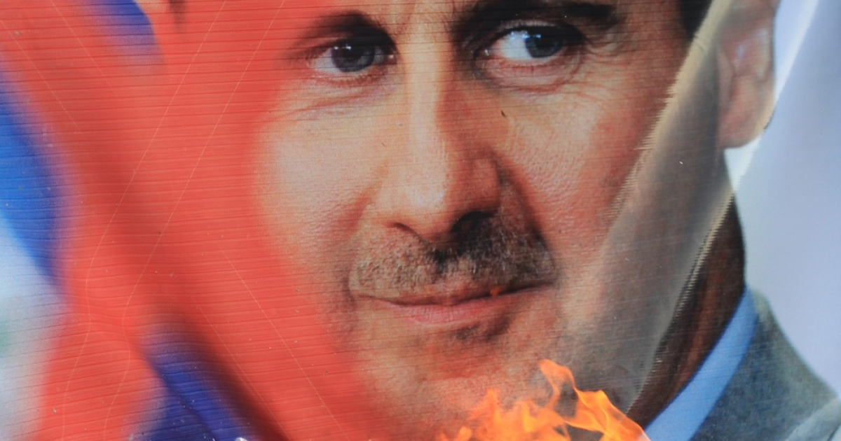 Pro-democracy protesters burn portraits of Syrian President Bashar al-Assad during a demonstration outside the Arab League headquarters in Cairo where an emergency ministerial meeting was held on November 12, 2011 to discuss the situation in Syria.</p>