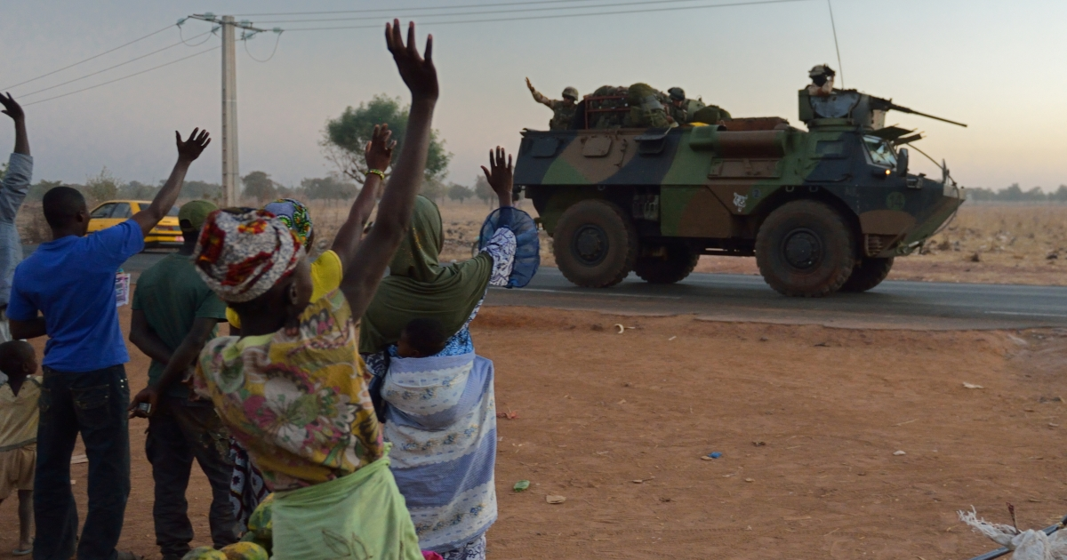 Malian people wave to French soldiers heading north from Bamako under the 'Serval' operation, on January 15, 2013. France is using air and ground power in a joint offensive with Malian soldiers launched on January 11 against hardline Islamist groups controlling northern Mali.</p>