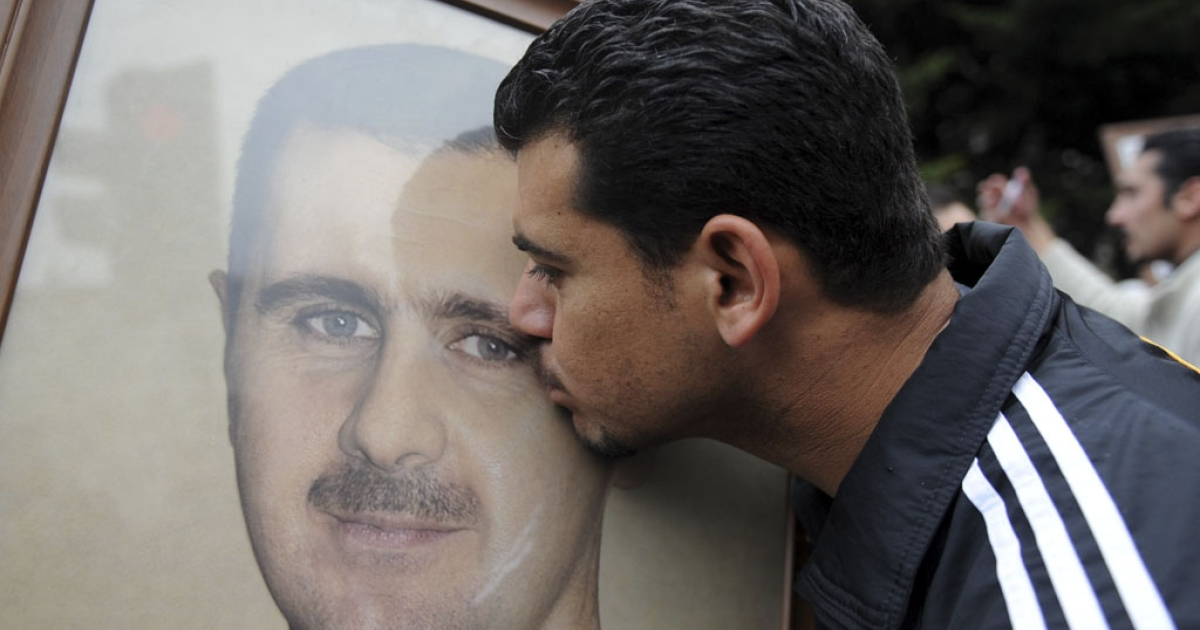 A President Bashar Al-Assad supporter kisses his portrait on April 1, 2012, outside the Istanbul Congress Center where the Friends of Syria conference was opening in Turkey.</p>