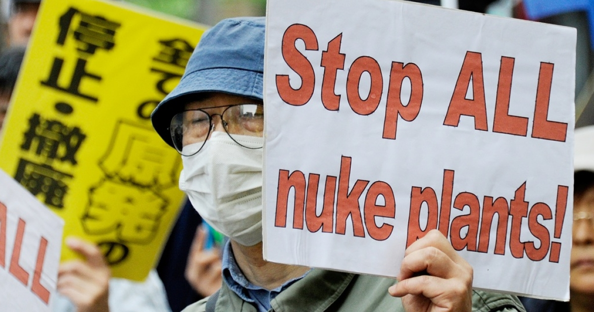 A man holds a placard during a march denouncing the use of nuclear plants and power during a May Day demonstration in Tokyo on May 1, 2011. Several hundreds of people took part in the May Day demonstration in the wake of the country's recent nuclear crisis at the Fukushima nuclear plant, north of Tokyo, damaged in the March 11 earthquake and tsunami.</p>