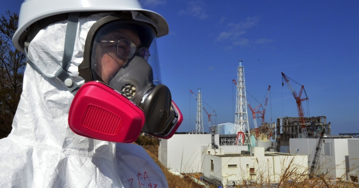 This file photo taken on February 28, 2012 shows a journalist looking at the stricken Fukushima Daiichi nuclear power plant in the town of Okuma, Fukushima prefecture.</p>