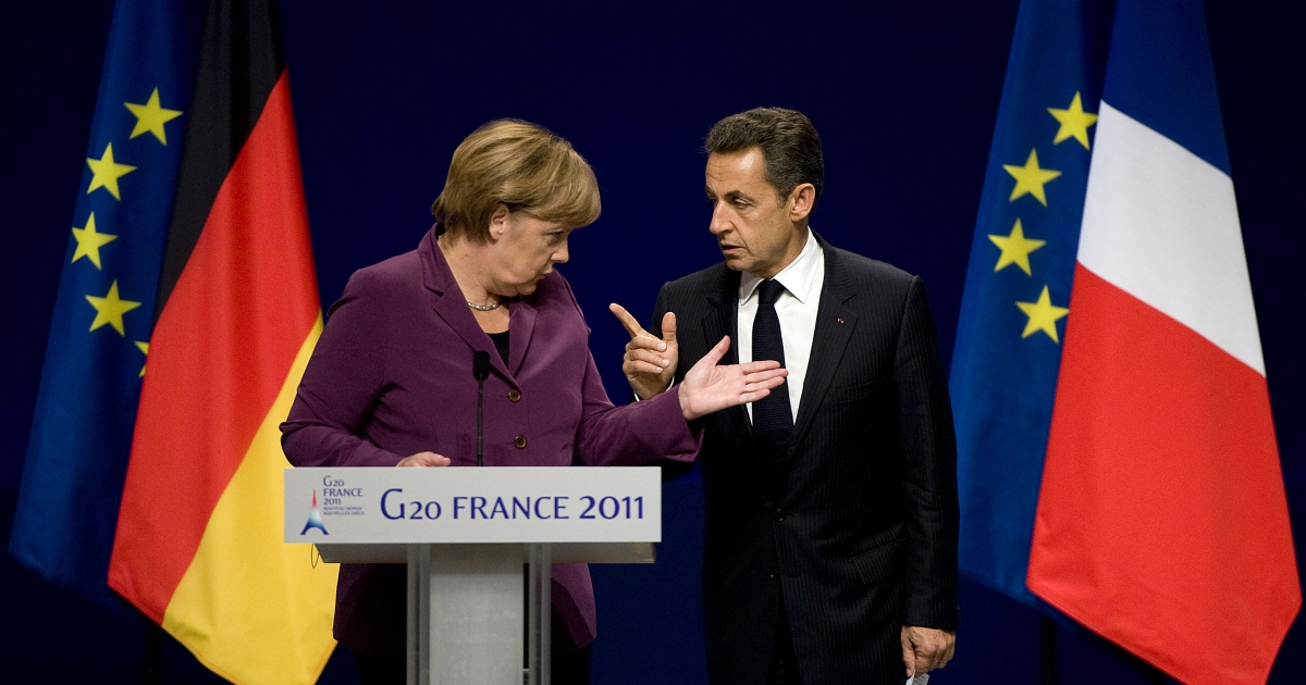 German Chancellor Angela Merkel and French President Nicolas Sarkozy talk as they arrive for a press conference after a meeting with Greek Prime Minister George Papandreou and EU and IMF representatives over Eurozone bailout plan ahead of the G20 summit on November 2, 2011 in Cannes, France.</p>