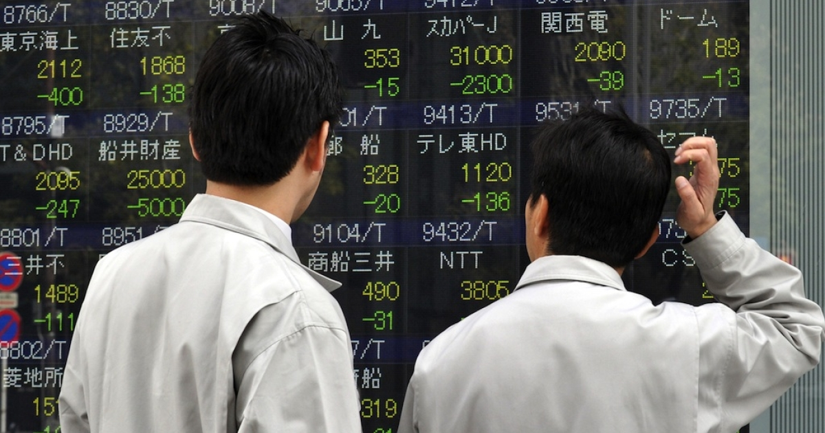 Businessmen look at a share prices board in Tokyo on March 14, 2011, showing a drop in the markets following the first full day of trading after the deadly March 11 earthquake and tsunami.</p>