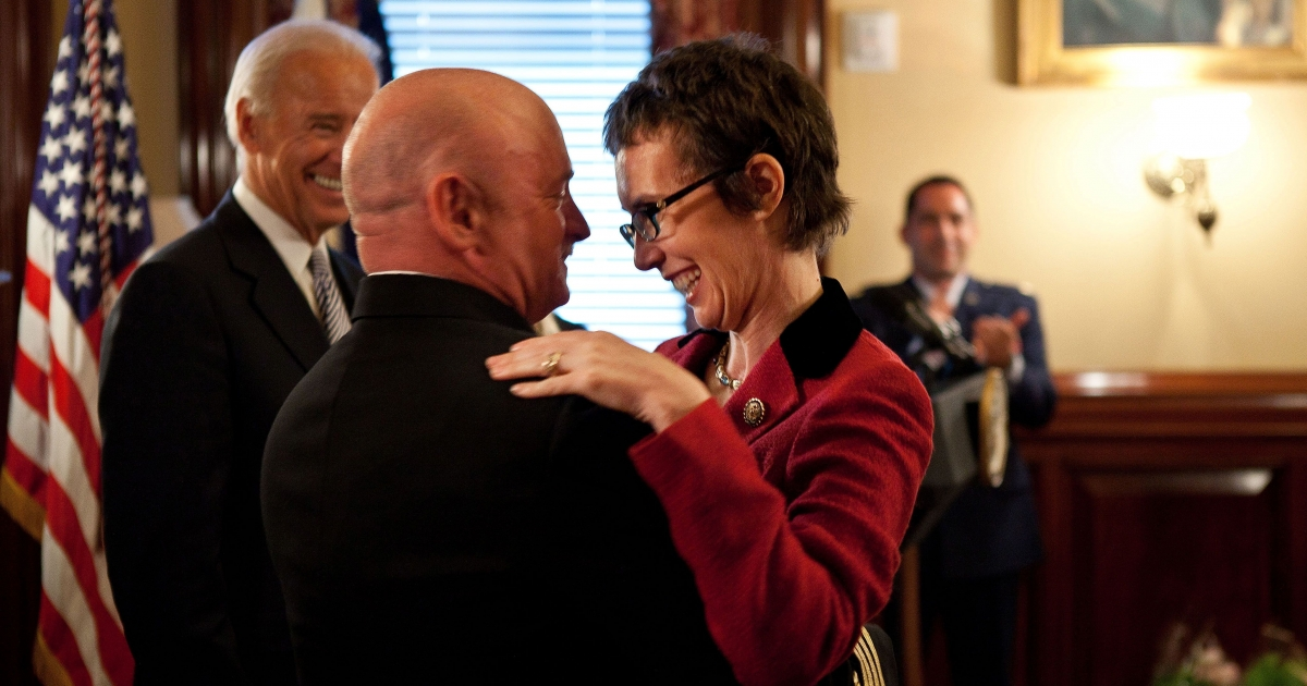 In this official White House photo, Captain Mark Kelly hugs his wife Congresswoman Gabrielle Giffords after receiving the Legion of Merit from Vice President Joe Biden during Captain Kelly's retirement ceremony in the Secretary of War Suite in the Eisenhower Executive Office Building, in Washington, D.C., Oct. 6, 2011.</p>