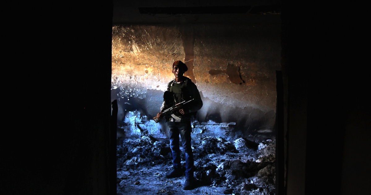 A rebel militiaman stands in the ashes of an alleged torture chamber of the former Libyan Internal Security force in Benghazi, Libya. Feb. 28, 2011. The notorious building was mostly burned in the uprising that drove loyalists to President Muammar Gaddafi out of Bengazi the week before.</p>