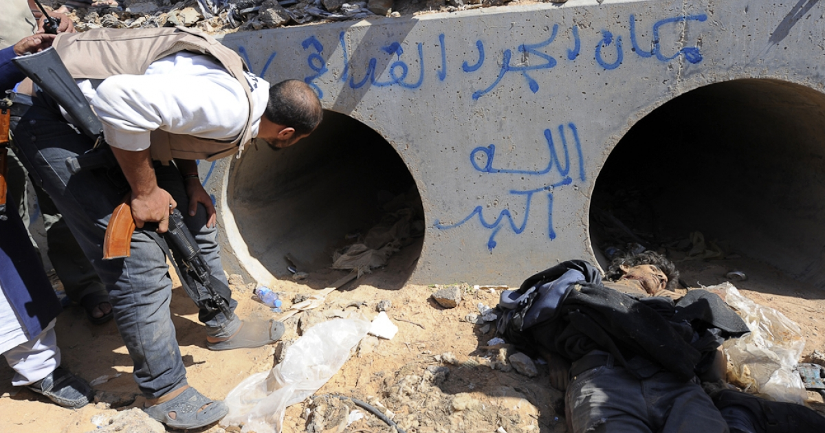 A Libyan National Transitional Council (NTC) fighter looks through a large concrete pipe where ousted Libyan leader Muammar Gaddafi was allegedly captured, with a dead loyalist gunmen in the foreground, in the coastal Libyan city of Sirte. Oct. 20, 2011.</p>